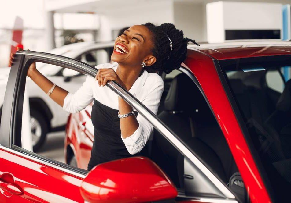 Woman buying the car. Lady in a car salon. Elegant black girl